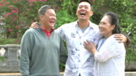 Senior Asian couple with adult son laughing in park