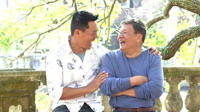 Senior Asian man and adult son talking, laughing in park