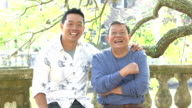 Senior Asian man and adult son talking, smiling in park