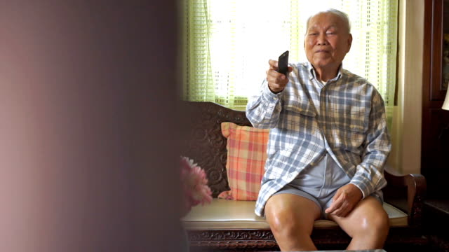 Senior Asian Man watching television and use remote