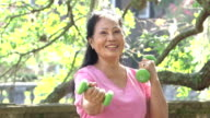 Senior Asian woman exercising in park with hand weights