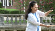 Senior Asian woman practicing tai chi in the park