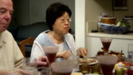 Senior Asian woman Talks while Dining with Friends