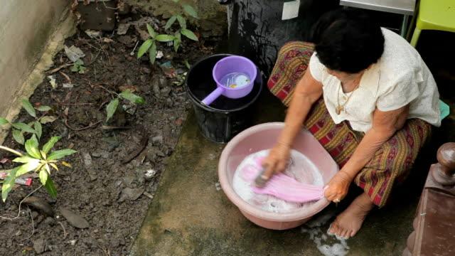 Ältere asiatische Frau Waschen Tücher von hand
