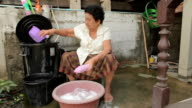 Senior asian woman washing cloths by hand