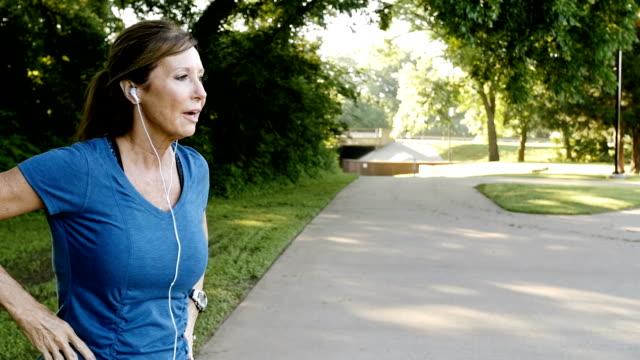 Senior athletische Frau auf dem richtigen Weg im Park Joggen und Zeit oder Puls überprüfen