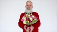 Senior bearded man with flowers on a white background.