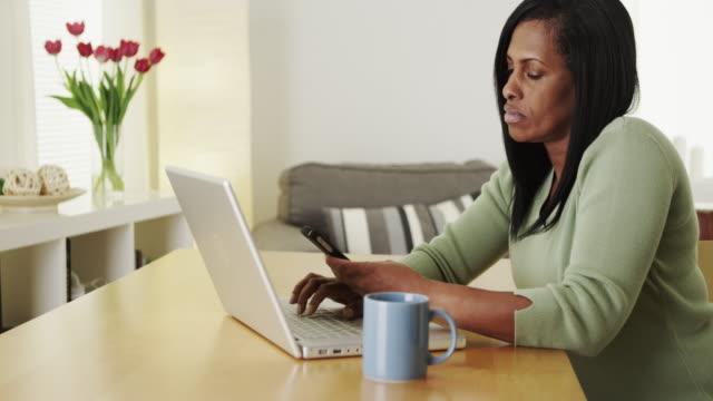 Senior black woman typing on laptop computer
