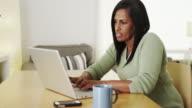 Senior black woman working on laptop computer at desk