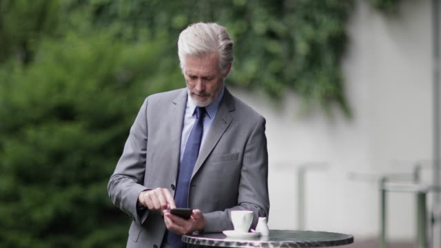 Senior business executive using a smartphone in a cafe outdoors