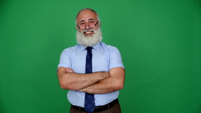 senior businessman looking into the camera with a smile and crossed arms on a green background