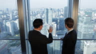 MS HA Senior businessman talking to young businessman standing by office window, cityscape in background / Beijing, China