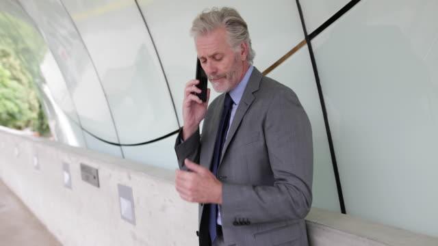 Senior businessman using smartphone outdoors