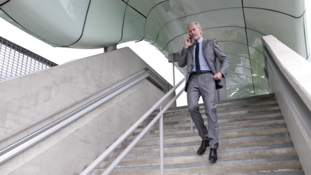Senior businessman walking down stairs using smartphone outdoors