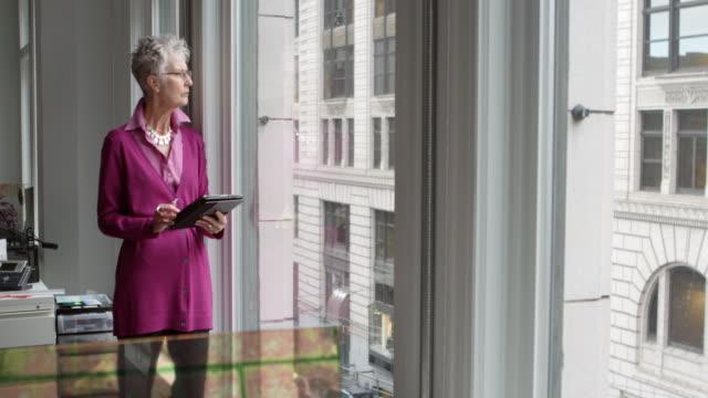 MS Senior businesswoman standing near window in office working on digital tablet