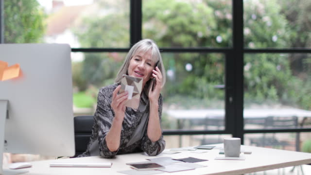 Senior businesswoman working in office using smartphone