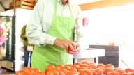 Senior Caucasian grocer examines tomatoes at produce market