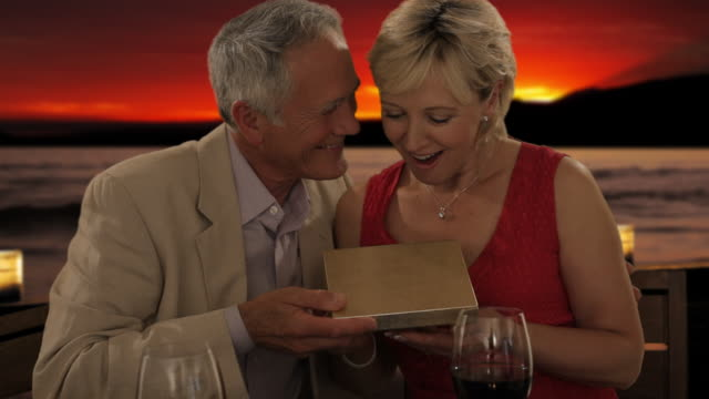 senior couple at dinner in sunset giving present of pearls