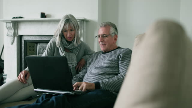 Senior couple at home using a laptop