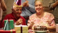 Senior couple celebrating birthday party with their friends