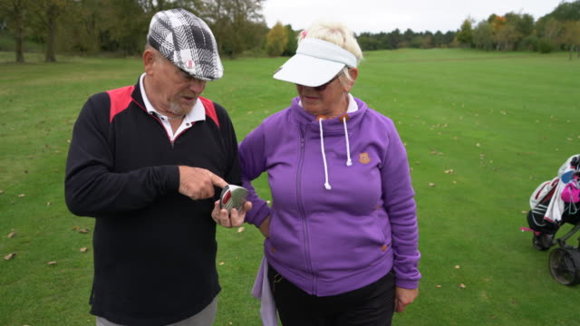 A senior couple checking their clubs on the course.