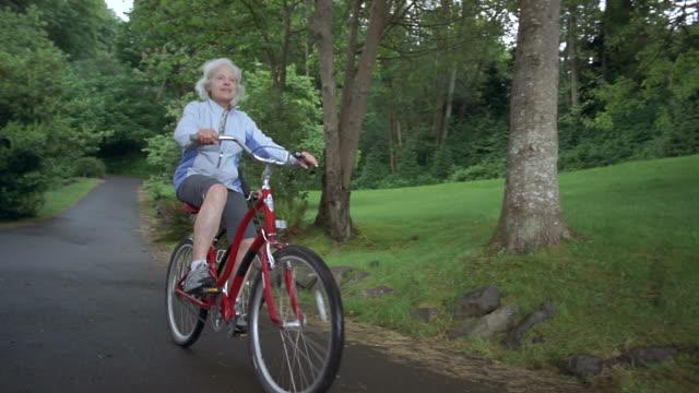 LA WS PAN Senior couple cycling on road in park / Washington State, USA