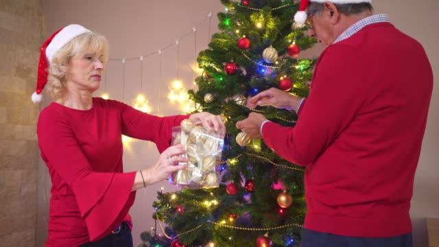 Äldre par dekorera julgranen