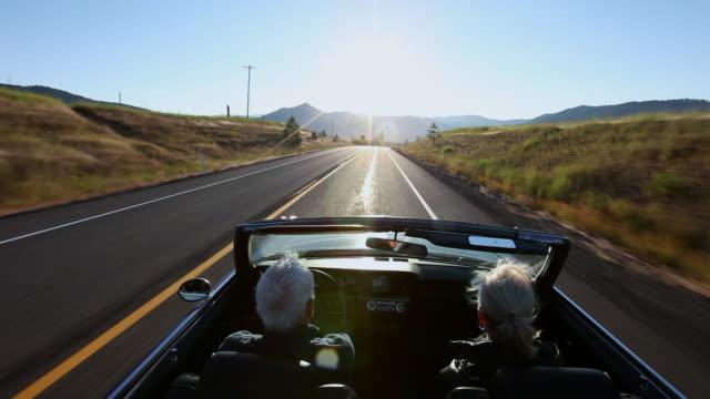 WS Senior couple driving convertible car at sunrise on rural road/Washington, USA