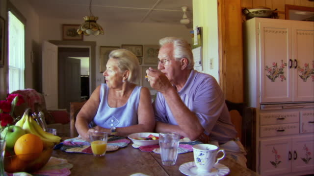 MS PAN Senior couple eating fruit salad in living room, Halifax, Nova Scotia, Canada