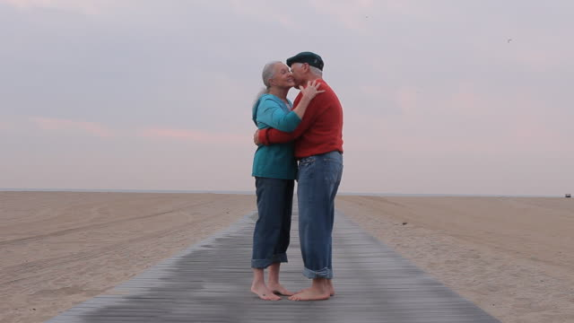 WS Senior couple embracing on beach boardwalk / Los Angeles, California, USA