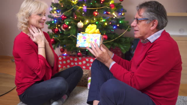 Senior couple giving each other Christmas presents