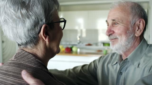 Senior couple hugging at home