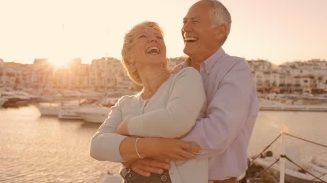 senior couple hugging by marina in sunset