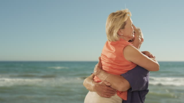 senior couple hugging on beach with sea background