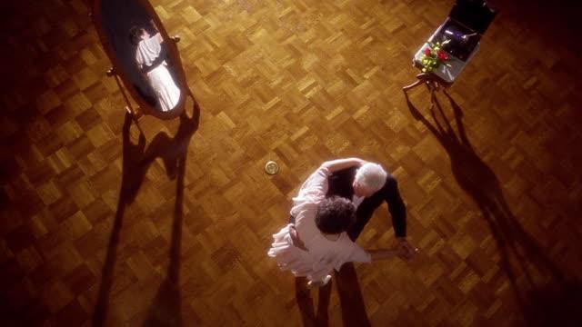 OVERHEAD senior couple in formalwear dancing on hardwood floor with mirror