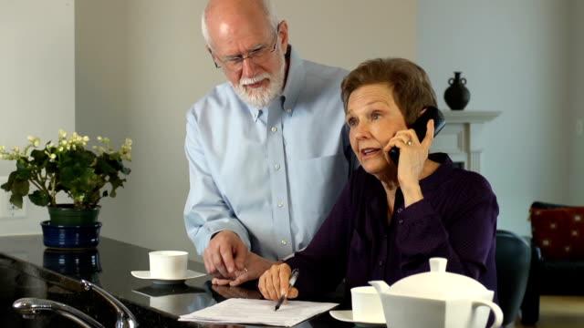 Senior paar communiceren op telefoon.