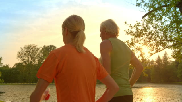 SLO MO TS Senior couple jogging along lake at sunset