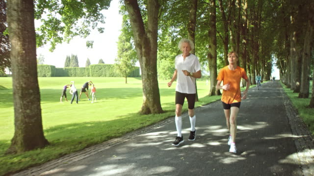 SLO MO TS Senior couple jogging through a park