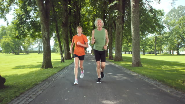 SLO MO TS Senior couple jogging through a sunny tree-lined lane