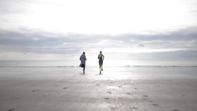 Senior couple jogging to coastline