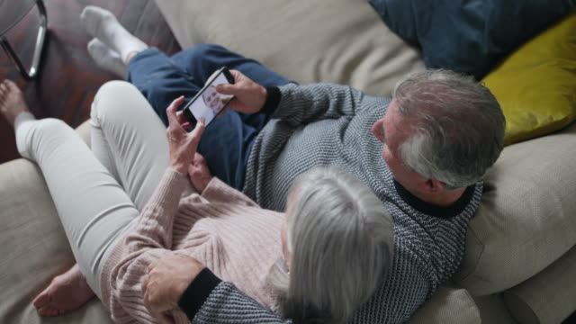 Senior couple looking at photo of daughter on a smartphone