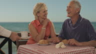 senior couple meeting at beach cafe by sea, waiter bringing coffee