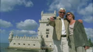 MS, Senior couple photographing self in front of Belem tower, Lisbon, Portugal