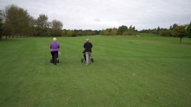 A senior couple playing golf. Walking away from camera on the fairway.