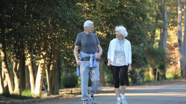 MS TU Senior couple power walking on tree lined street / Richmond, Virginia, USA