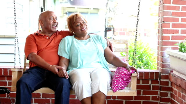 Senior couple relaxing, talking on porch swing