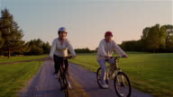 Senior couple riding bicycles on dirt road at sunset