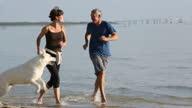 senior couple running on beach with dog