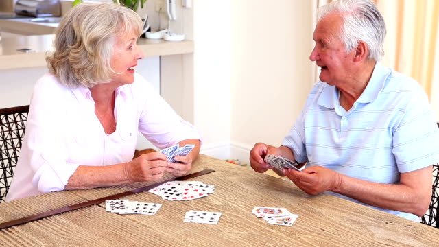 Senior couple sitting at table playing cards