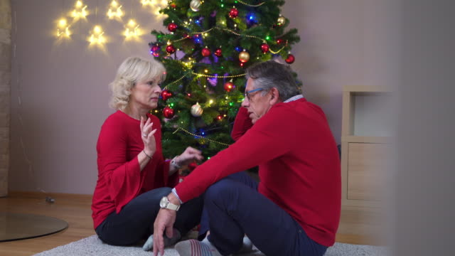 Senior couple sitting in front of a Christmas tree and talking